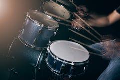 L'homme joue le tambour réglé à l'arrière-plan de faible luminosité Photo stock