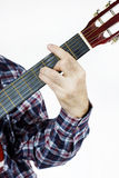 L'homme joue une corde sur la guitare Photos stock