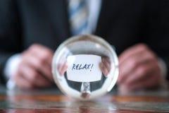 L'homme jugeant de papier avec le mot détendent devant la boule en verre Photo libre de droits