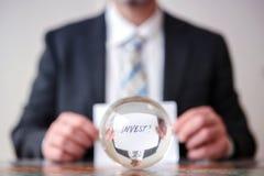 L'homme jugeant de papier avec le mot investissent devant la boule en verre Photos libres de droits