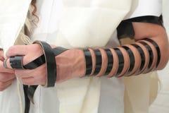 L'homme juif enveloppé dans le tefillin prient Un juif orthodoxe religieux avec le bras-tefillin sur sa main gauche prie Images stock
