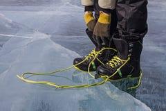 L'homme lace faisant du surf des neiges les chaussures lumineuses sur la glace avec ses gants tricotés images libres de droits