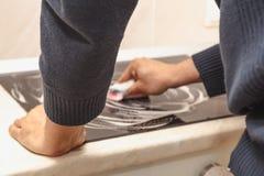L'homme lave le fourneau électrique noir moderne avec du savon Nettoyez la Chambre Photo stock