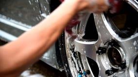 L'homme lavent la roue de la voiture banque de vidéos