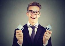 L'homme libre d'affaires de dette tenant une carte de crédit a coupé dans deux morceaux Photos stock
