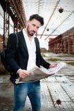 L'homme lit le journal sur la rue Images stock