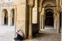 L'homme lit le Quran dans la cour de la grande mosquée dans Kairouan, Tunisie photos stock