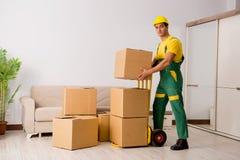 L'homme livrant des boîtes pendant le mouvement de maison Photographie stock