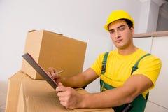 L'homme livrant des boîtes pendant le mouvement de maison Photo stock