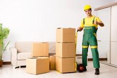 L'homme livrant des boîtes pendant le mouvement de maison Photos libres de droits
