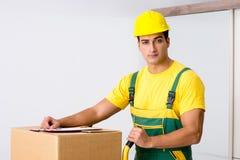 L'homme livrant des boîtes pendant le mouvement de maison Photos stock