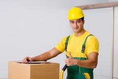 L'homme livrant des boîtes pendant le mouvement de maison Image stock