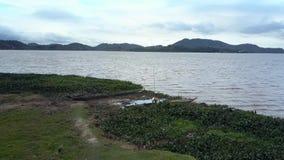 L'homme local place la voile de canoë de pirogue sur le lac au crépuscule banque de vidéos