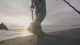 L'homme méconnaissable avec le détecteur de métaux électronique recherche des trésors sur la plage tropicale de sable d'océan ave banque de vidéos