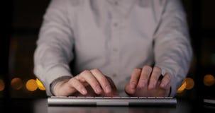 L'homme méconnaissable dactylographie sur le clavier se reposant à la table sur le lieu de travail dans l'obscurité Remet le plan banque de vidéos