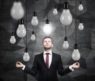 L'homme méditant recherche de nouvelles idées Un bon nombre d'ampoules Fond contemporain foncé Photos stock