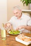 L'homme mûr aîné mangent de la salade végétale Image stock