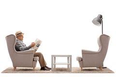 L'homme mûr a assis dans un fauteuil lisant un journal Photo stock