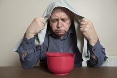 L'homme mûr avec un froid et un sinus publie inhaler la vapeur Images stock