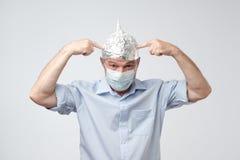 L'homme mûr caucasien dans un chapeau de papier d'aluminium et le chapeau médical a contrarié la dissimulation de la vie extérieu photos stock
