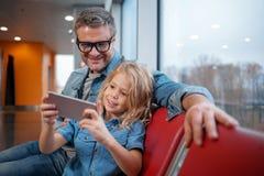 L'homme mûr et la petite fille utilisent le téléphone portable Images libres de droits