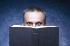 L'homme mûr focalisé et accroché par le livre, lisant le livre ouvert, a étonné le jeune homme, yeux étonnants semblant la couver Images stock