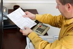 L'homme mûr regardant la feuille d'impôt impriment  photos stock