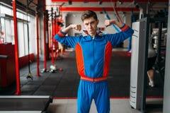 L'homme maigre dans les vêtements de sport montre ses muscles, gymnase photos libres de droits