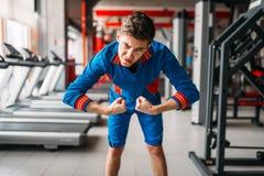 L'homme maigre dans les vêtements de sport montre ses muscles, gymnase photos stock