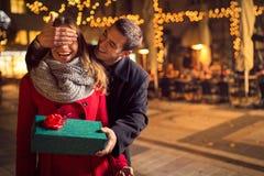 L'homme maintient ses yeux d'amie couverts tandis qu'elle donnant un cadeau Photos stock