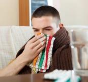 L'homme malade dans le plaid utilise le mouchoir Photographie stock libre de droits