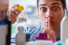 L'homme malade malade recherchant des médecines à l'étagère de farmacy Image stock