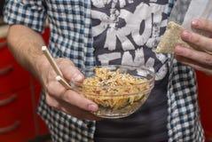 L'homme mange du riz frit avec des baguettes pour des sushi Photographie stock