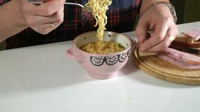 L'homme mange les nouilles instantanées chinoises avec une fourchette banque de vidéos