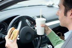 L'homme mange un hamburger et boit un soda tout en conduisant sa voiture images libres de droits
