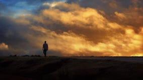L'homme marche à travers l'horizon avec le ciel mobile de coucher du soleil banque de vidéos
