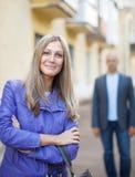 L'homme marche derrière la femme sur la rue Image stock