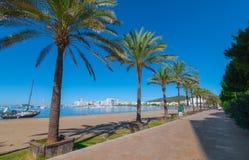 L'homme marche en un voilier abandonné sur la plage Les rangées de la ligne de palmiers arrosent le bord du ` s dans Ibiza Image stock
