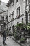 L'homme marche par dans une rue du village français médiéval du Saint-Guilhem-le-Désert images libres de droits