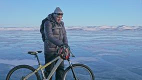 L'homme marche près de la bicyclette sur la glace Le cycliste est habillé dans une veste, un sac à dos et un casque de gris vers  clips vidéos