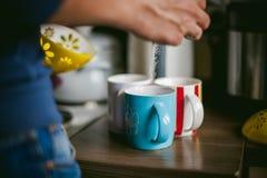 L'homme marié avec un anneau sur son doigt, préparent votre café de matin au petit déjeuner pour sa famille Images stock