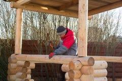 L'homme martèle le rail en bois dans le faisceau photo libre de droits