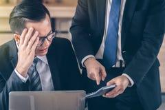 L'homme masculin d'affaires est blâmé par un patron qui tient une calculatrice photos libres de droits