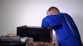 L'homme masculin d'ingénieur de technicien installent la carte mère de PC dans la caisse noire banque de vidéos