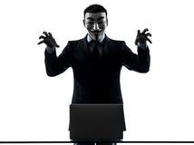 L'homme a masqué l'ordinateur de calcul de membre anonyme de groupe menaçant le SI photographie stock
