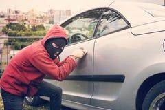 L'homme masqué s'accroupit et casse quelqu'un voiture regardant à la visionneuse Le voleur dans le hoodie et le visage caché fait images stock