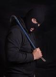 L'homme menaçant avec un passe-montagne masquent et tenir un pied-de-biche Image stock