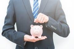 L'homme met des pièces de monnaie dans le concept porcin de l'épargne de banque-le image stock