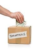 L'homme met l'argent dans la boîte en carton de donations avec le billet de banque du dollar Photographie stock libre de droits