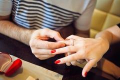 L'homme met la femme une bague de fiançailles en café Photos libres de droits